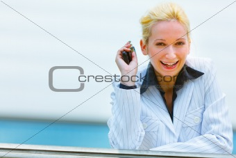 Smiling business woman with mobile in hand leaning on railing at office building