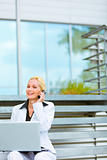 Smiling business woman with laptop sitting on stairs at office building and talking on mobile