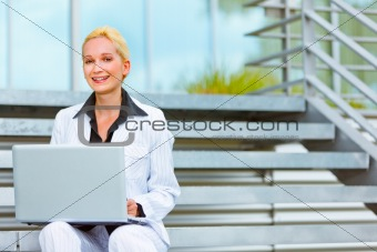 Smiling business woman sitting on stairs at office building and using laptop