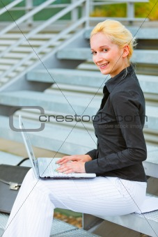 Smiling business woman sitting on stairs at office building and working on laptop