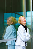 Laughing business woman with crossed arms on chest at office building