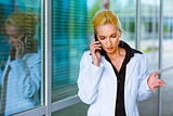 Concentrated business woman talking on mobile at office building 