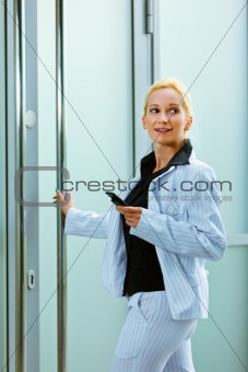 Smiling business woman entering office building holding mobile in hand