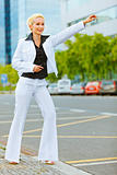 Smiling business woman catching taxi near office center