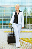 Travelling smiling business woman with suitcase 