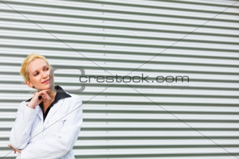 Smiling business woman standing at office building and looking at copyspace