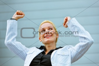 Excited  business woman standing at office building  and rejoicing her success