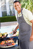 Man Enjoying A Barbequed Meal In The Garden