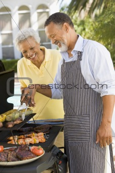 Couple Cooking On A Barbeque