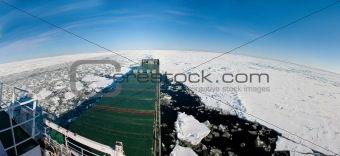 Panoramic shot of a ship navigating in ice.
