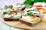 snacks sandwiches with egg and anchovies on a wooden board