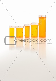 Several Different Sized Empty Medicine Bottles as Increasing Graph on Reflective Surface.