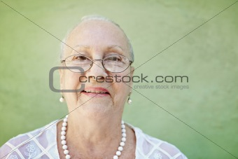 aged woman with white hair smiling at camera