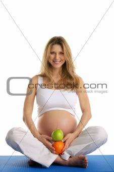 Pregnant woman practicing yoga and keeps fruit