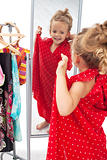 Happy little girl trying on dresses in front of mirror