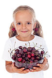 Little girl with cherry earrings holding a bowl of fresh fruits