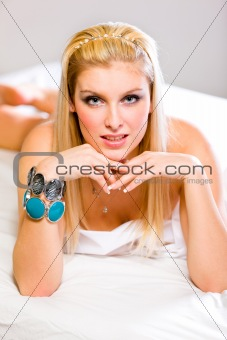 Portrait of sensual beautiful girl with blonde hair and expressive eyes lying on bed