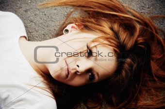 Portrait of beautiful young girl lying on asphalt