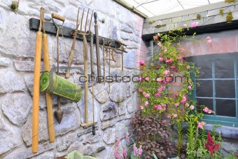 garden tools on stone wall