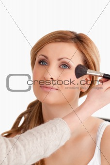 Make-up artist applying make up to an attractive woman