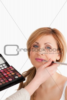 Young blond-haired woman having her make up done by a make up ar