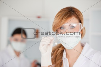 Blond-haired scientist holding a test tube looking at the camera
