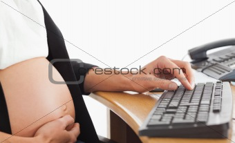 Pregnant woman on the phone working with a computer