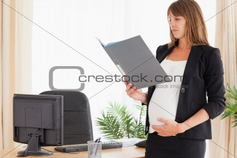 Beautiful pregnant female holding a file while standing