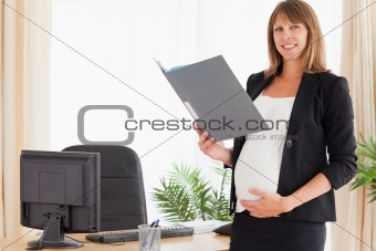 Attractive pregnant female holding a file while standing