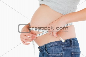 Pregnant woman measuring her belly while standing