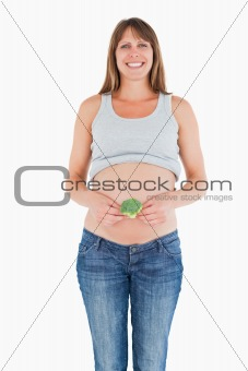 Beautiful pregnant woman holding a broccoli while standing