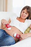 Gorgeous pregnant female playing with red baby shoes while lying