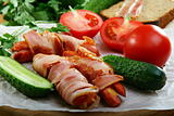 Sausages wrapped in bacon with vegetables and herbs.