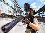 Paintball player over industrial background