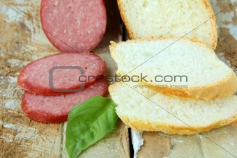 white baguette and salami on a wooden table