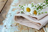 bouquet of daisies on the linen bag  on a wooden table rustic still life