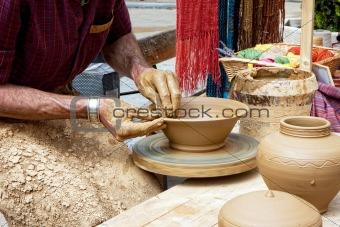 Potter works a potter's wheel