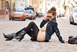 fashionable girl sitting on the street