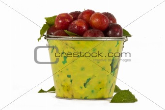 red plums in yellow bucket
