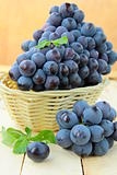 Brush black sweet grapes in a basket on wooden table