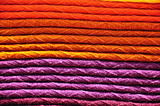 Stack of traditional woven alpaca blankets in orange and purple