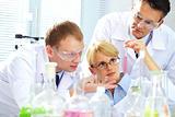 Three chemists researching liquid in tubing