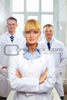 Portrait of female doctor standing in front of her male colleagues