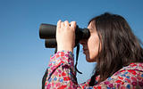 Young woman using binoculars 