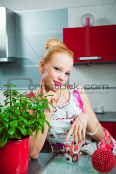 Blond girl with glass in interior of kitchen