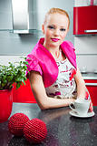 Blond girl in interior of red modern kitchen