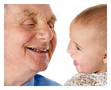 Portrait of grandfather and granddaughter, smiling at each other