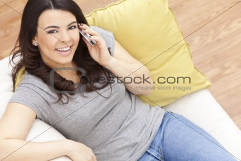 Happy Hispanic Woman Using Cell Phone At Home