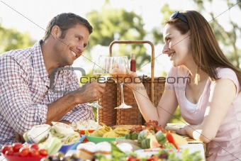 Couple Eating An Al Fresco Meal, Toasting With Wineglasses