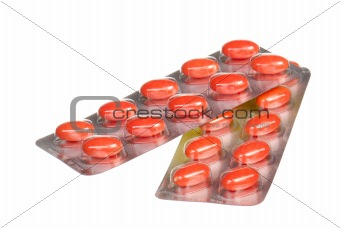 close up orange capsules and blisters isolated on white